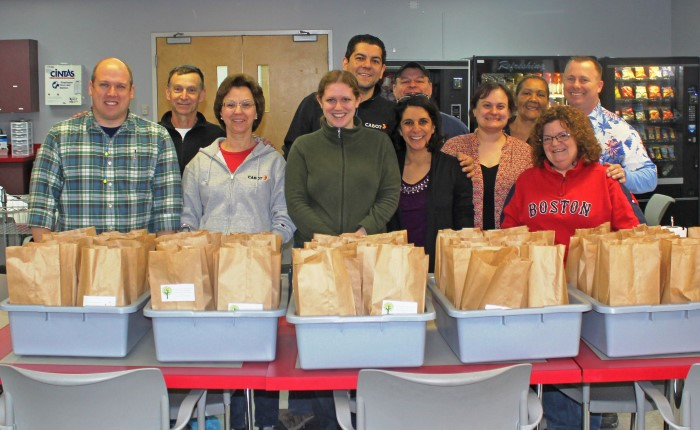 About 12 Cabot employees behind several bins of brown bagged meals