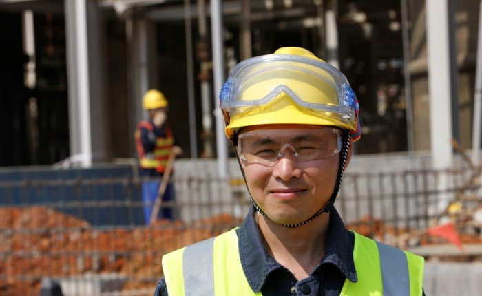 Cabot employee outside a facility wearing a hard-hat, goggles, and safety vest
